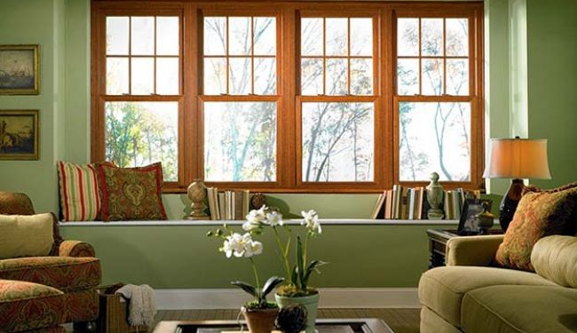 Single hung sliding windows, brown wood frames, set in green living room
